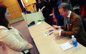 David Zyla signing a student's program.